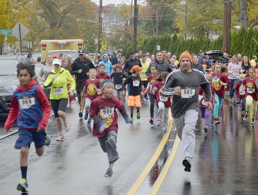 Entrants in the Fanwood Family Fun Run, part of the borough's 5K race activities, stream under the Fanwood Fire Dept.'s large American flag on LaGrande Avenue in Fanwood, NJ, Sunday, Oct. 25, 2015. (Photo by Brian Horton)