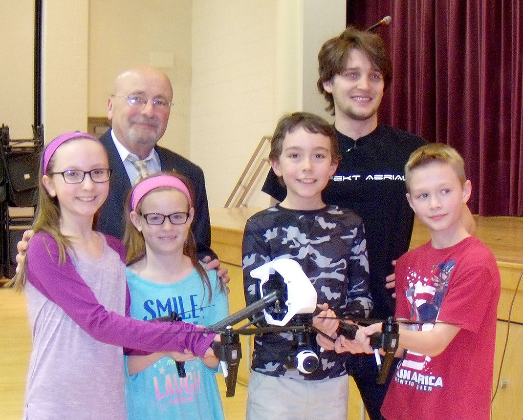 (above back l-r) Irene E. Feldkirchner (IEF) Elementary School Principal Armand Lamberti joins Connor Leszczuk, of Aspekt Aerial, Verona, during an IEF Elementary School assembly all about drones. (front, l-r) Madeline Mills, Paige Thomas, David Schreck and Michael Dumiec – are all IEF students who were up close to examine a drone. The students commented on how much they enjoyed the presentation and demonstration, citing how amazingly light drone materials can be, how uses of drones span from hobbyist to the commercial industry and how they can be used for search and rescue.