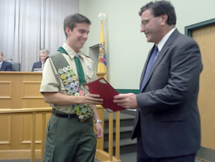(above, r-l) Mayor Paul Mirabelli handing a copy of the proclamation to Ryan Bonk commemorating his rank as Eagle Scout at Mountainside Borough Hall.