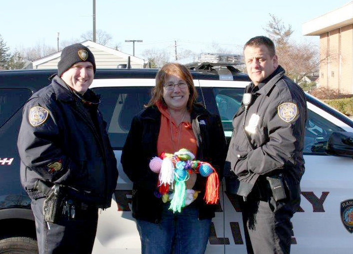 "(above l-r) Rahway Police Officer Robert Zarzycki, Sharon Young and Police Officer TJ Salvia accepting the ""Blanket Babies"" for use in Rahway Police vehicles."