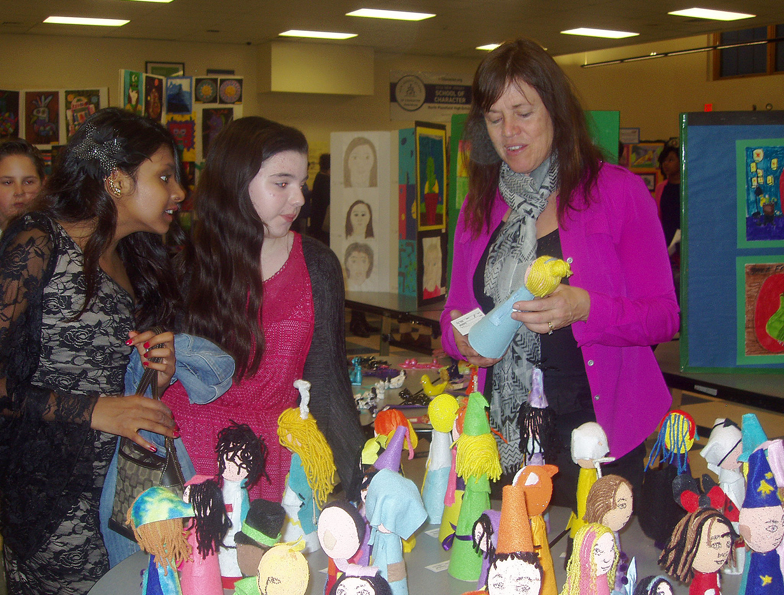 "(above) North Plainfield High School Ceramic and Somerset Intermediate School Art teacher Kathie Fry pictured with from left to right sixth graders Farah Baijnath and Nicole Lindemeyer – as they view the 3-D art forms called ""Wizards."""
