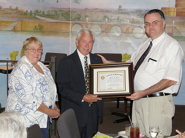 """(above r-l) Rotary President-Elect Michael Castoral presents a """"Certificate of Membership"""" to new honorary member Harry Allen, accompanied by his wife, Janice."""