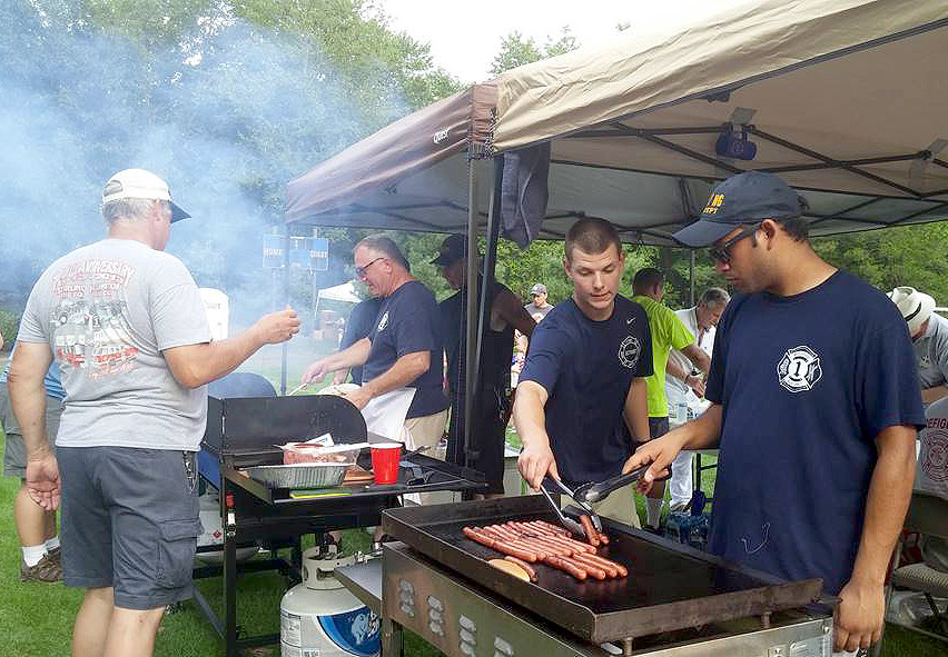 (above) Neil Vaish (front right) of the Stirling Fire Department grills hot dogs and hamburgers provided free of charge to attendees.