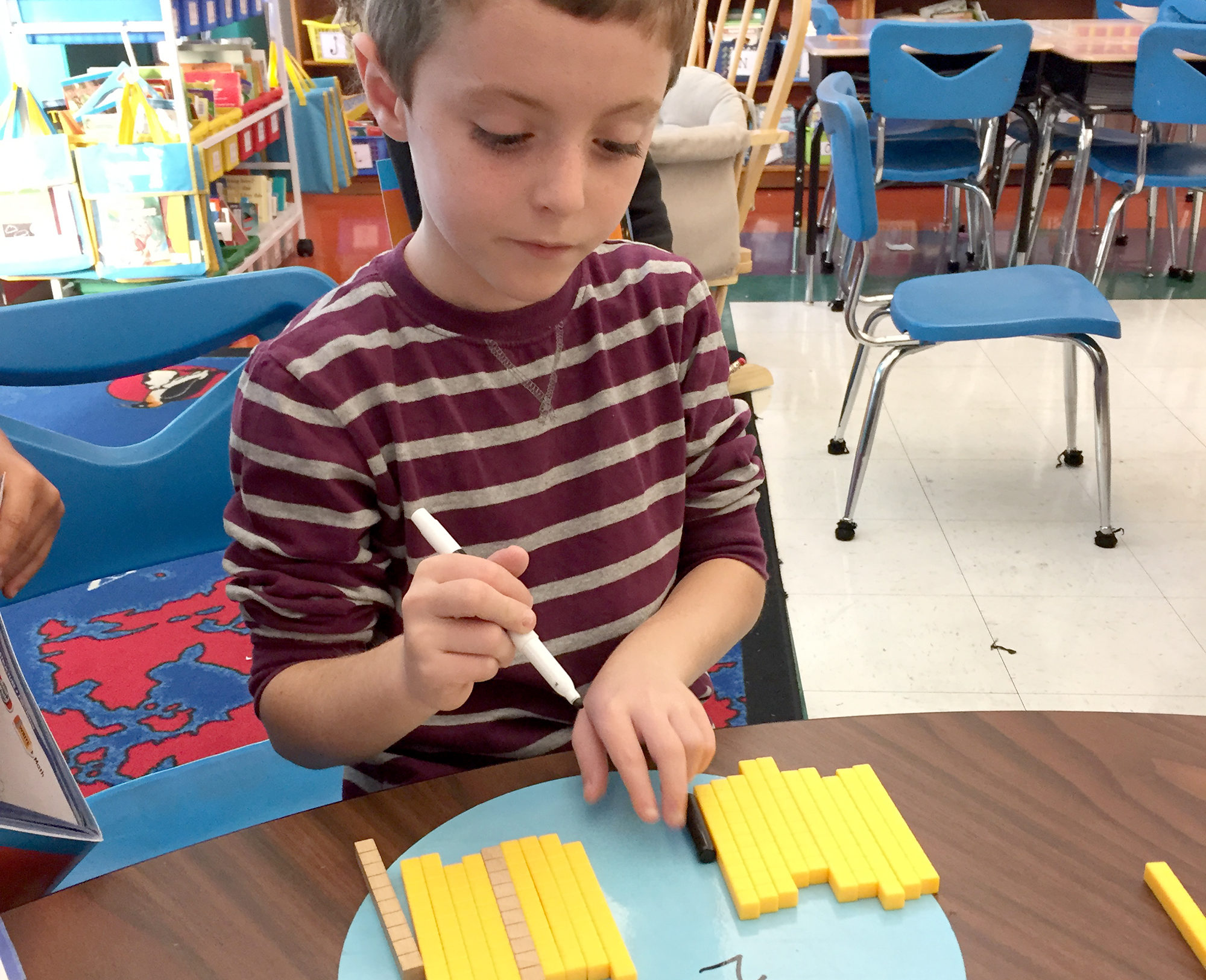 (above) Students use blocks to understand place value and to model, write, and compare 3-digit numbers in Mrs. Bakker's 2nd grade class. Manipulatives, models, pictures, and symbols are used to build mathematical understanding as part of the Go Math! program. The program helps students engage with the Common Core State Standards.